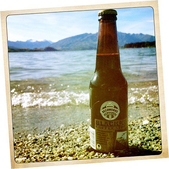 Image of bottle of Black Peak Coffee Stout on the shores of Lake Wanaka, NZ