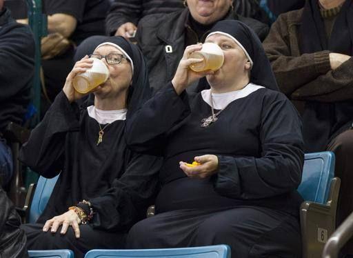 Due suore bevono bicchieri di birra allo stadio durante un match di curling, a Kamloops, in Canada