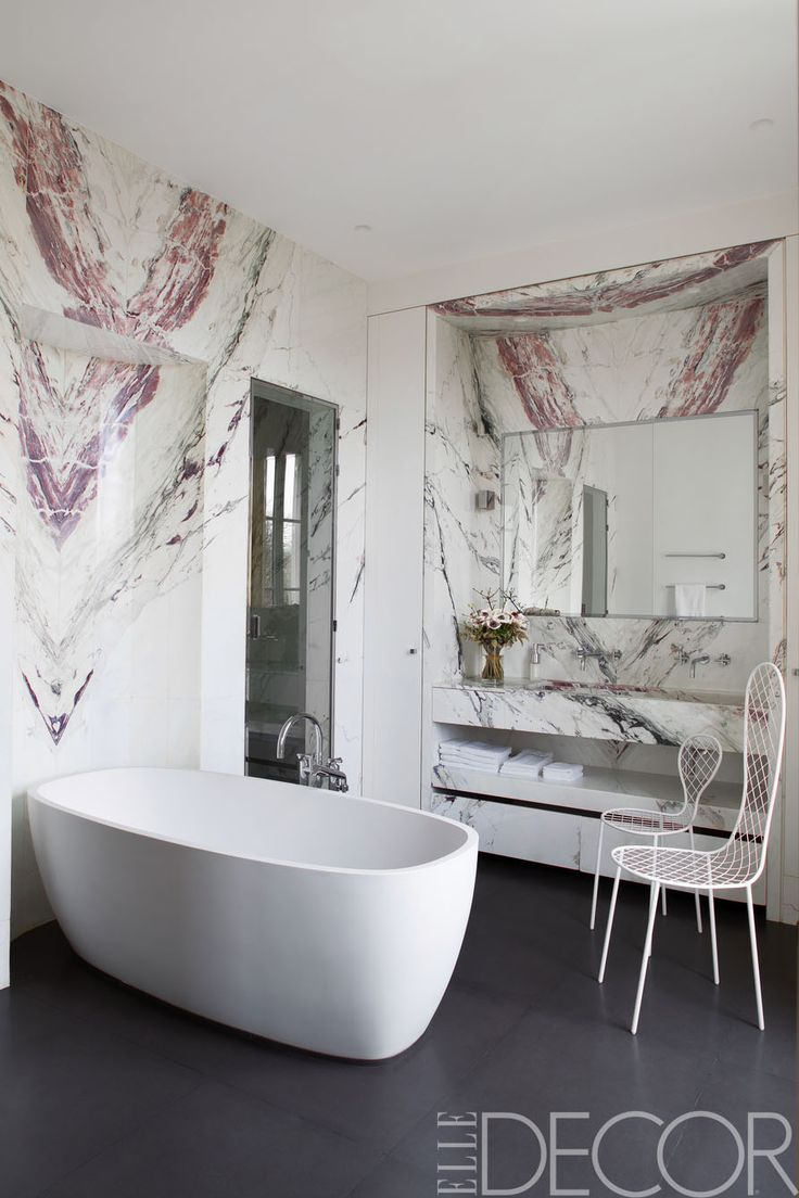 The tub in the master bath of this Paris apartment is by Agape, with fittings by Dornbracht, the chairs are by Junya Ishigami, the walls are clad in Brèche de Médicis marble, and the flooring is granite. - ELLEDecor.com