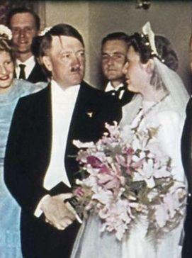 Actually this is May, 1939 and Hitler is merely the honored guest at a wedding. He had attended the shotgun wedding of Hermann Esser the previous month. The left photo shows Hitler's lover, Eva Braun, peeking out from the second row.