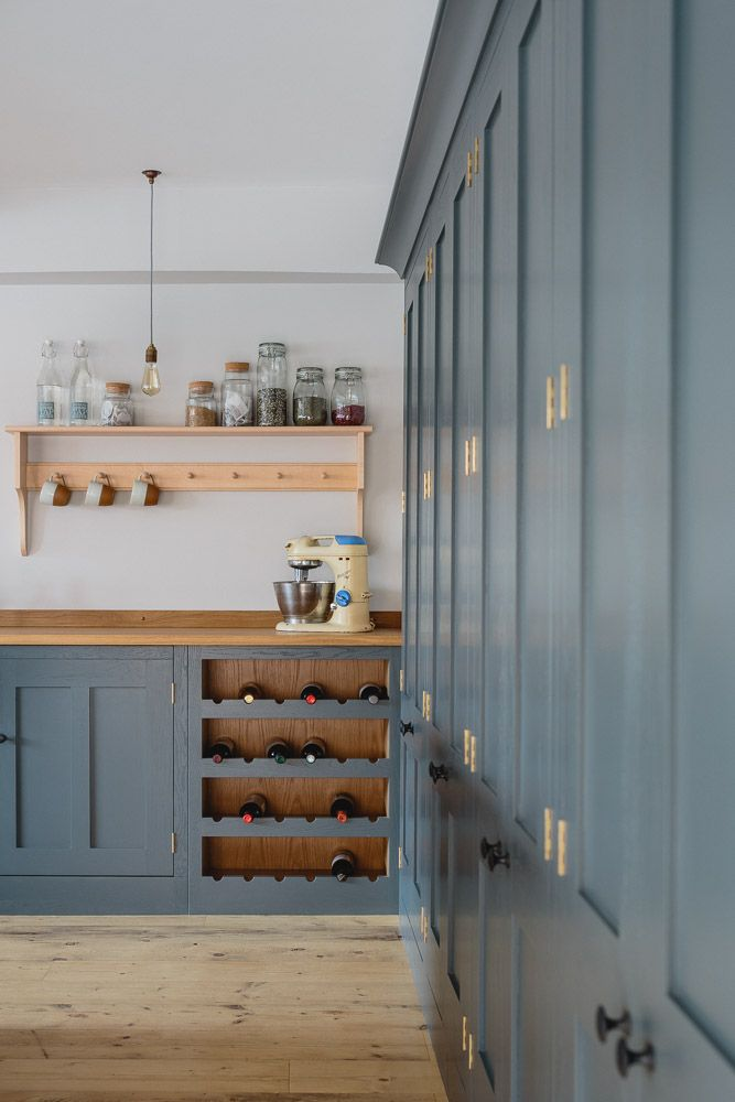 Industrial Shaker style showroom oak kitchen painted in Farrow & Ball Down Pipe. There is a dedicated wine storage area built into the base cabinets with a birch shaker peg shelving above. The base cabinets have an oak worktop. The tall larder cabinets are visible along with the reclaimed scaffold plank flooring.