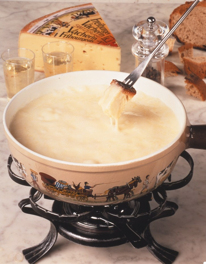 Fondue is a popular winter dish in Switzerland.  The caquelon (fondue pot) is first rubbed with a cut clove of garlic.  A mixture of cheeses, usually including Gruyere and Emmentaler, white wine, and kirsch are heated and kept warm in the caquelon.  Long handled forks are used for dipping cubes of crusty bread into the fondue.