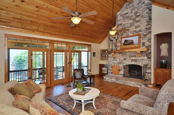 stacked stone fireplace in living room with vaulted