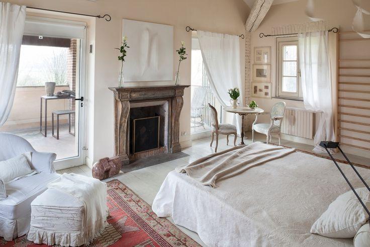 www.bebrelaisilvignolo.it Camera da letto del Relais Il Vignolo con pareti tinteggiate a calce, pavimento in larice, travi di rovere e  un antico camino francese in legno.