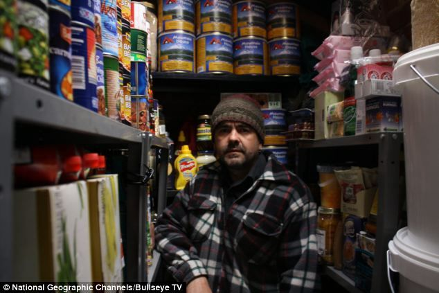 Prepared: Father-of-five Simon Dillon, pictured, stands in his store cupboard which is full to the rafters with emergency supplies