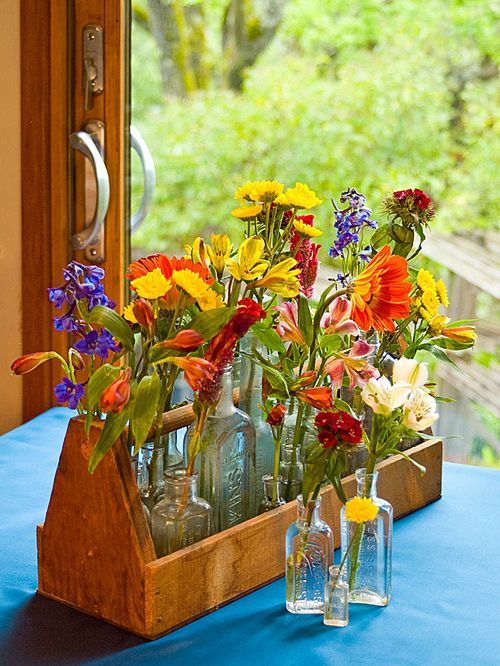 To maximize the impact of a collection, display all the pieces together in an unusual way. Two dozen apothecary bottles become an eye-catching centerpiece when placed in a rustic tool caddy. Add colorful wildflowers and a trendy turquoise tablecloth for a modern look with a homey feeling.