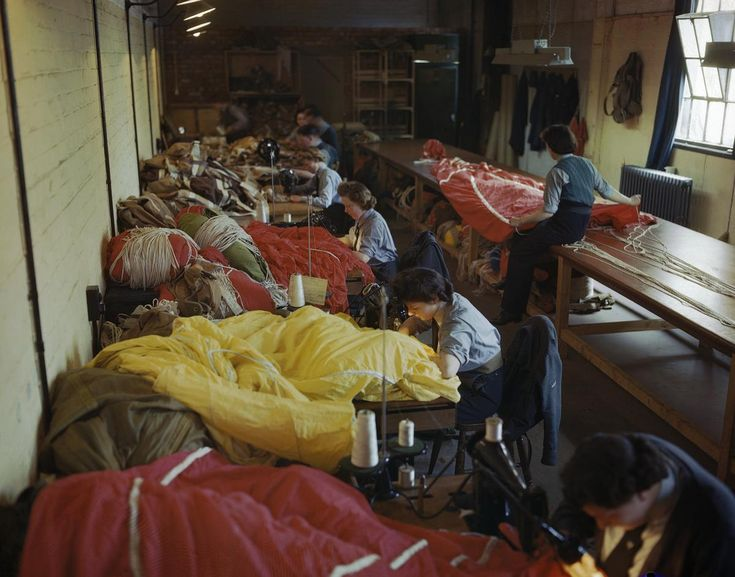 Members of the Women's Auxiliary Air Force (WAAF) repair and pack parachutes for use by airborne troops during the Normandy invasion, 31 May 1944