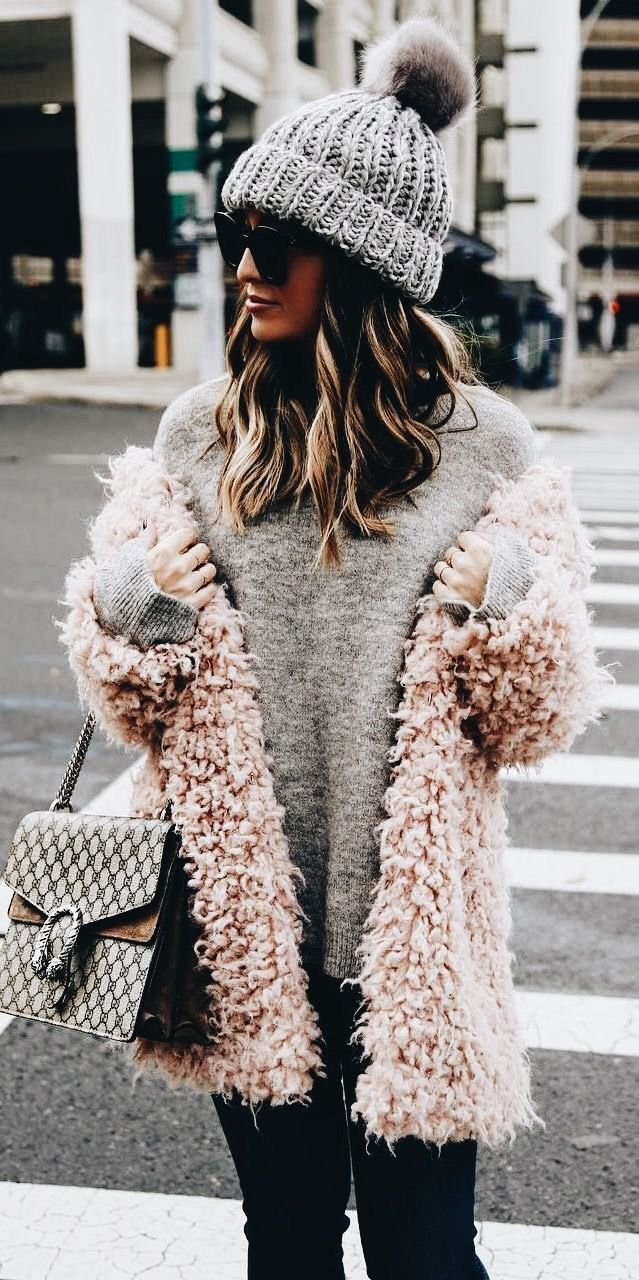 Soft pink shaggy jacket over gray sweater and black jeans with chic handbag.