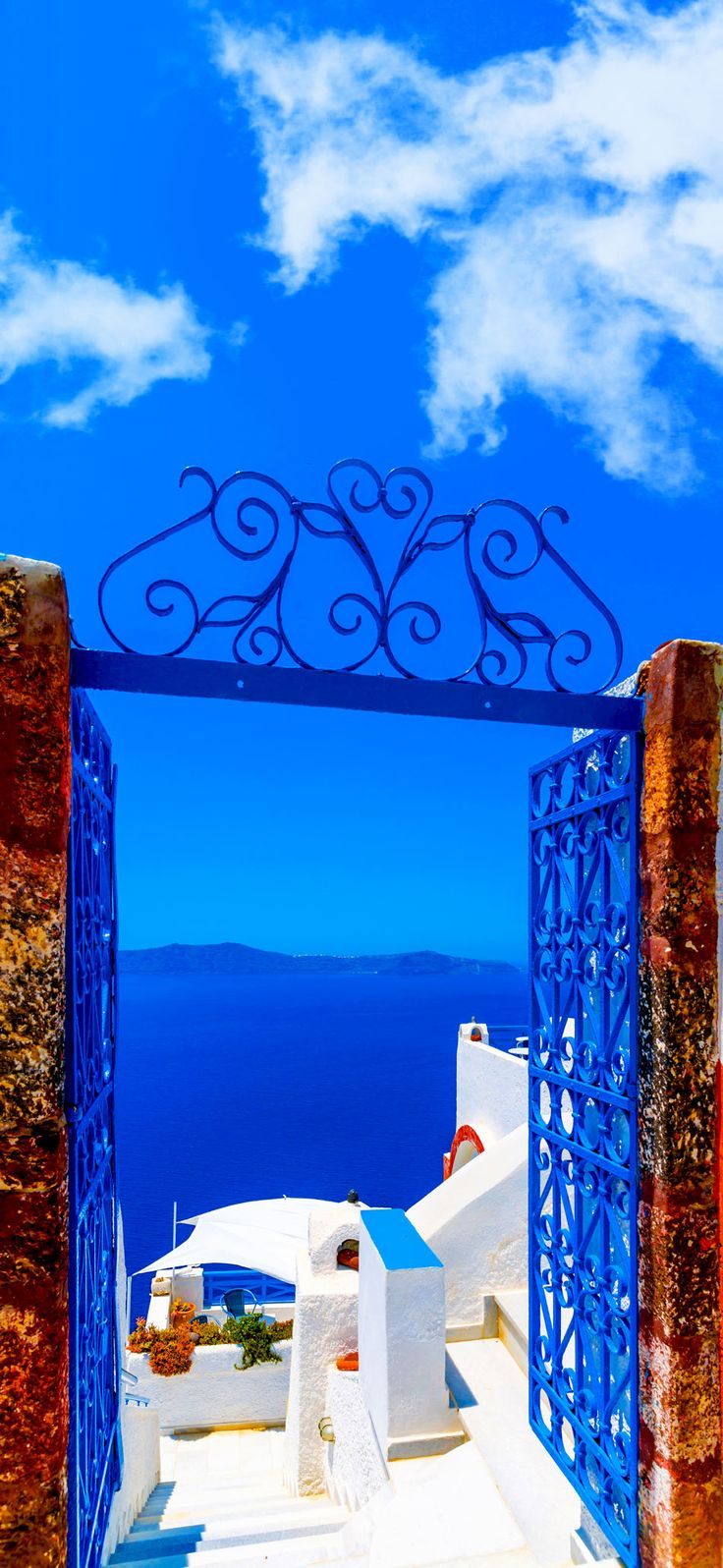 View to the sea and Volcano through a door, from Fira the capital of Santorini island in Greece    |    10 Breathtaking Photos of World's Most Romantic Island