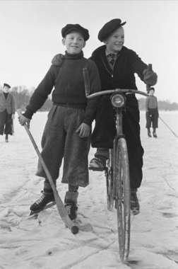 Brunnsviken, Stockholm. Två pojkar på isen. Den ene bär en bandyklubba, den andre sitter på en cykel och håller armen om sin kamrat. 1936. Fotograf: Lundh, Gunnar