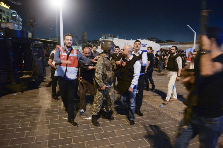 A Turkish police officer, right, confronts a Turkish army officer, left, that participated in the coup, after he was apprehended in Istanbul's Taksim square, early Saturday, July 16, 2016