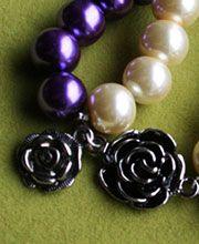 EL BOSQUE DE ALSEIDE: Pulsera en perlas violetas y color crema, con accesorios (rosas) plateados.