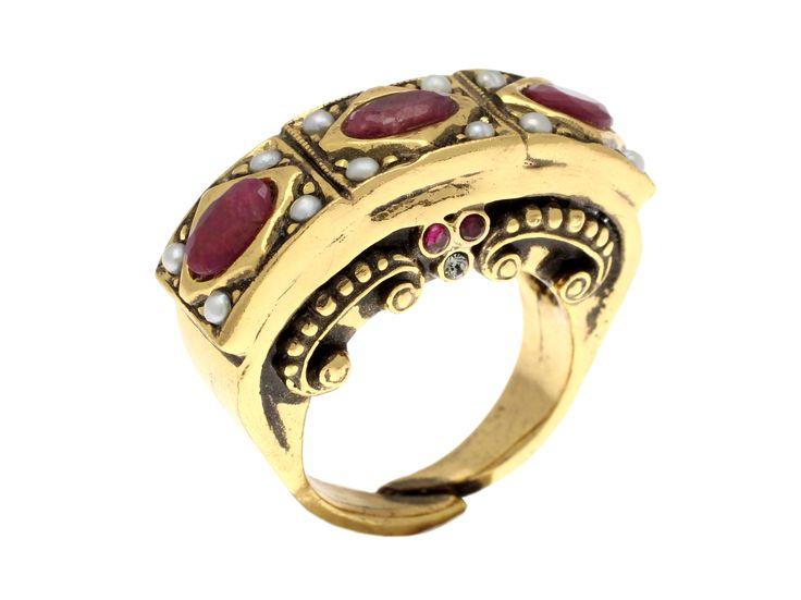 Винтажное кольцо из коллекции Classic, напоминающее старинные итальянские украшения. Крупные тёмно-розовые рубины окружены симметричными белыми жемчужинами, вся архитектура кольца подчёркнуто геометрическая. Изделие выполнено из ювелирного сплава, покрытого золочением и патинированием, размер регулируется.