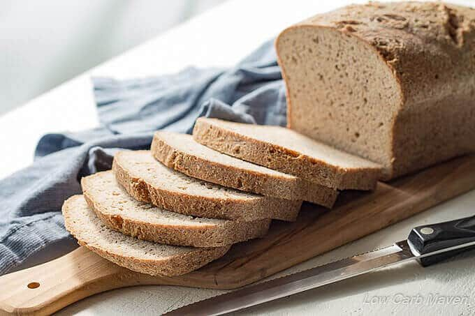 A sliced loaf of flax bread sitting on a handled cutting board between a knife and a blue napkin.
