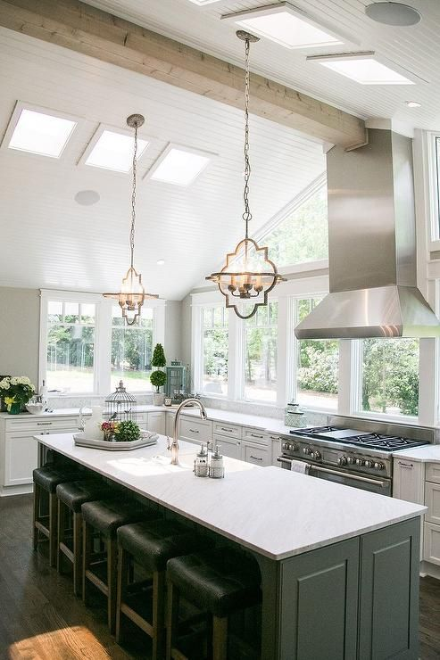 White and gray kitchen features a vaulted ceiling accented with beadboard trim accented with skylights and a stainless steel hood, placed in front of a bank of windows, and a stainless steel stove.