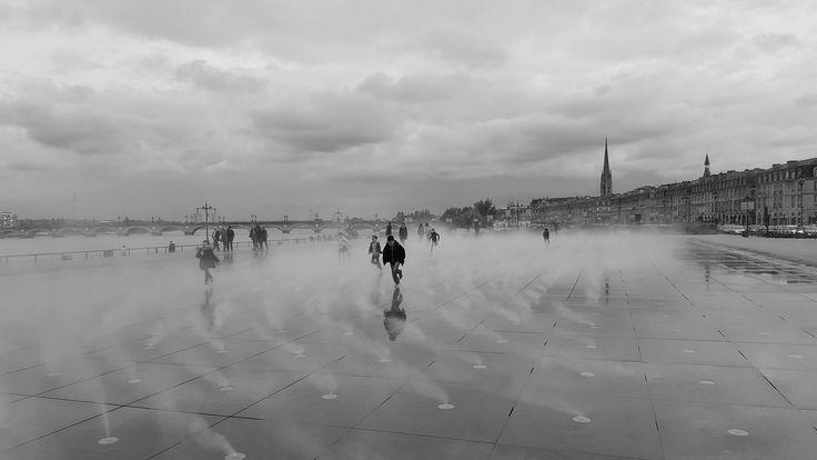 shot van spelende kinderen bij de Waterspiegel in Bordeaux. Elke paar minuten 'spuit' deze fontein een waternevel omhoog. Dit levert zeer mooie taferelen op. - Bordeaux, Frankrijk | Columbus Travel