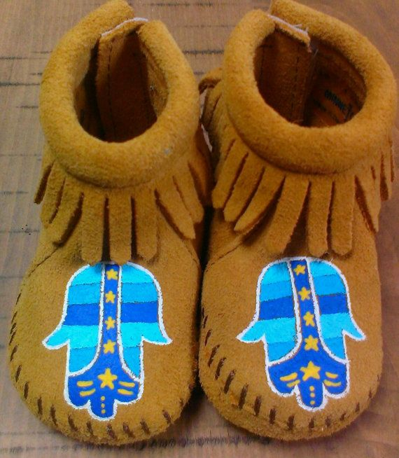 Custom, handpainted, one-of-a-kind, childrens Hamsa design on Minnetonka baby leather moccasins size 1 infant through 6. Fringe can be left unpainted (as shown) or painted with coordinating colors.  Free Range Mama is a free-hand, completely custom, hand-painted collection of keepsake baby booties and moccasins! My personalized shoes make the best baby shower gifts, Christmas and Holiday gifts, New Sibling gifts, etc! Please browse my Etsy shop for design inspiration and to see past custom…