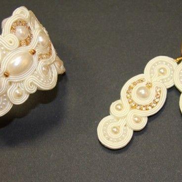 Komplet ślubnej biżuterii sutaszsoutache składający się z bogato zdobionej bransoletki oraz kolczyków. Wykonany pracochłonną techniką haftu sutasz ze szklanych perełek, taśmy cyrkoniowej w złotej oprawie, koralików toho, a także elementów pozłacanych. Całość w kolorze ecru (odcień mleczny). Biżuteria dla kobiety ceniącej elegancję i piękno ręcznie robionej biżuterii.  www.KuferArt.pl