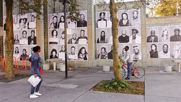 """Passers by view the new international art project launched by French conceptual artist JR called """"Inside Out"""" outside of the Dudley branch of the Boston Public Library in Roxbury. The project features portraits of Roxbury residents."""