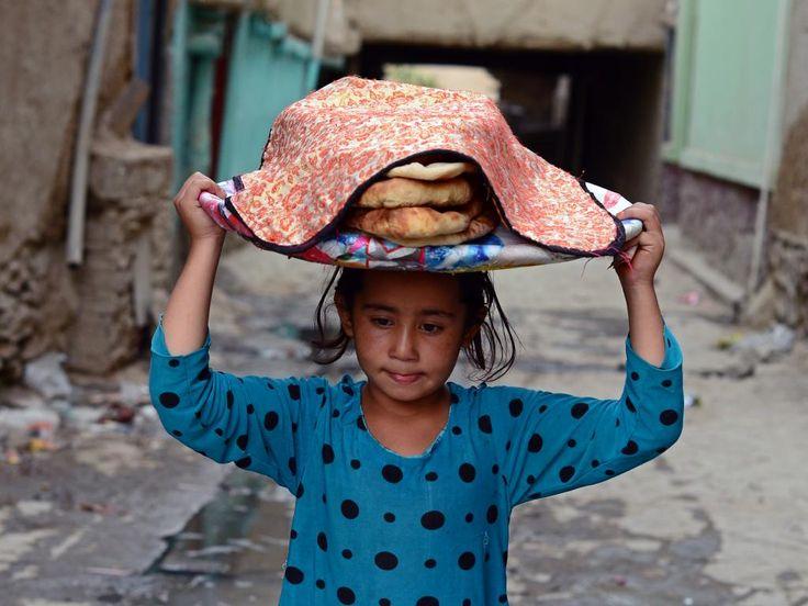 Dinsdag 2 september: Een Afghaans meisje draagt een mand met brood op haar hoofd in het oude gedeelte van Kabul.