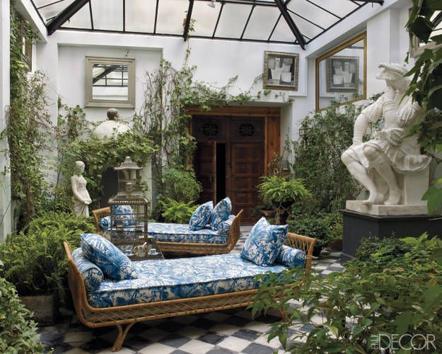 Spanish Conquest: In the courtyard, 1960s Jansen daybeds are upholstered in a Madeleine Castaing fabric, the cast of a Michelangelo sculpture is from a Paris flea market, and the Gothic Revival doors are 19th-century Spanish.