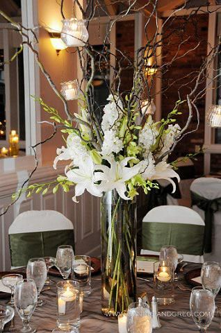 gorgeous #centerpiece, featuring white Casablanca lilies, white stock, green dendrobium orchid sprays and curly willow branches with hanging votive candles