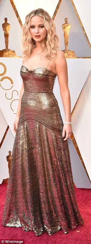 Gorgeous: Jennifer Lawrence wowed in her gold gown that had a textured fabric and delicate...