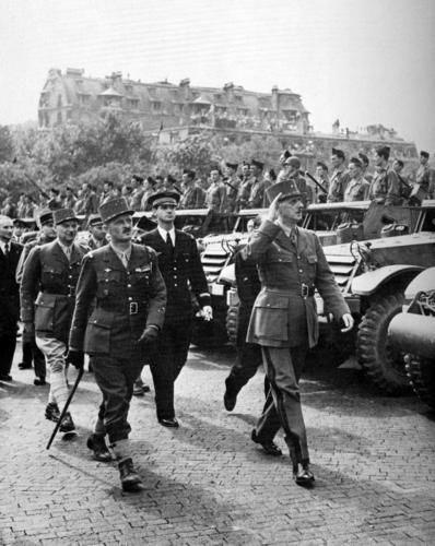 On August 26, 1944, just before the start of the victory parade, General de Gaulle (saluting) inspects troops of the French 2nd Armored Division with General Leclerc (walking stick).