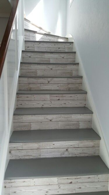 Basement steps: grey floor paint on the top of the steps and wood wall paper on the back part of the steps.