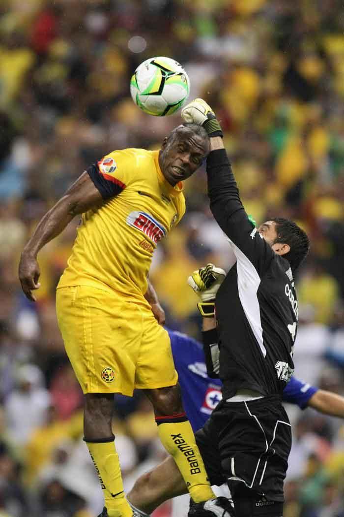 Benítez (i) disputa el balón con el portero José de Jesús Corona (d) de Cruz Azul.