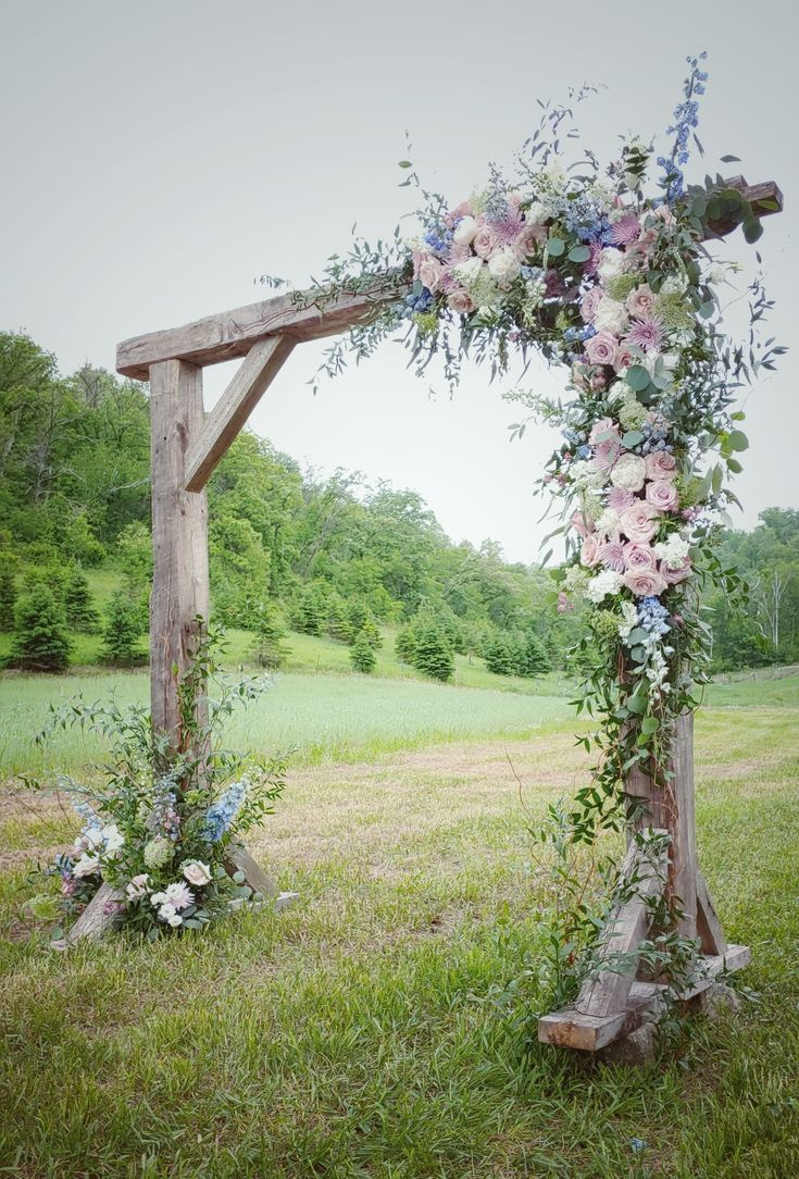 I designed this wedding arch as if the floral, Italian ruscus greens and curly willow were overgrown onto the arch from the ground up. It's as if the arch had always been there as nature grew in and around it. This is a delightful blend of light blue delphinium, blush peonies, lavender mums, Quicksand and Faith roses, white stock and white lisianthus.
