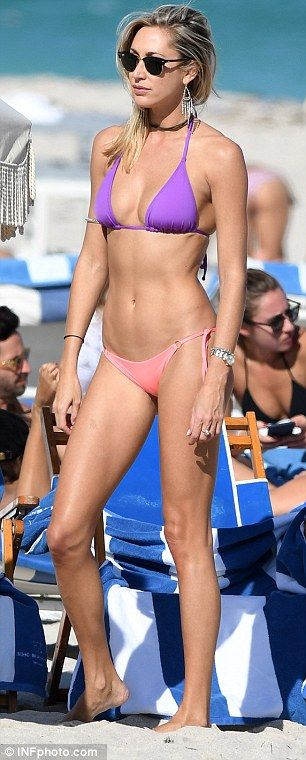 Blonde bombshell: Teamed with a pair of miniscule, low-cut pink bikini bottoms, the blonde beauty drew attention to her pert bottom and washboard abs