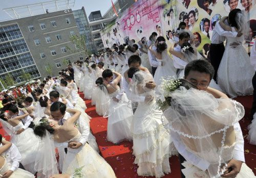China sets Olympics record in weddings, as 300,000-plus couples tie knot. Chinese couples kiss during a mass wedding ceremony in Wuhan, central China's Hubei province on 08 August 2008. China claimed it set a world record for marriages on a single day to coincide with the opening of the 2008 Beijing Olympic Games, with some 14,591 couples registered in Beijing alone.