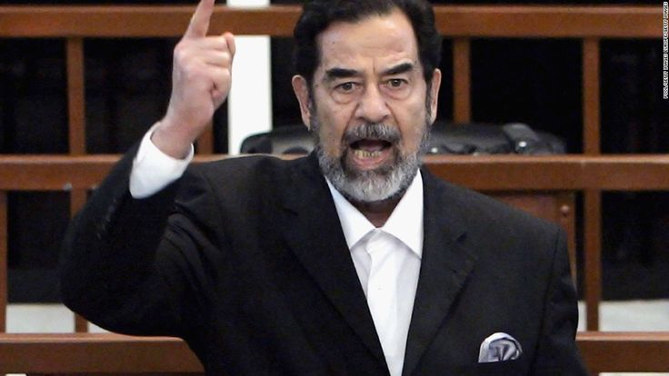"""Former Iraqi President Saddam Hussein as he receives his guilty verdict during his trial in the fortified """"green zone,"""" on November 5, 2006 in Baghdad, Iraq."""