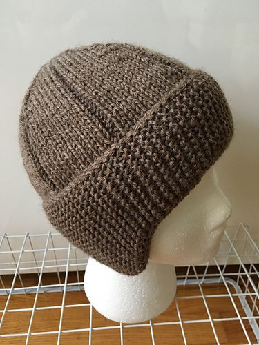 The construction of this hat was inspired by one pictured in a magazine published around 1910. Knitting the headband side to side provides a double layer of garter stitch to keep the ears warm, and allows for easy shaping of the earflaps. The edges of the headband are folded together along a slipped stitch seam, and picked up together to finish in the round. The hat has plenty of depth so it can be pulled low on the forehead, and the earflaps will naturally cup around the ears to keep them…