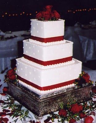 2 tier instead...buttercream and maybe a more substantial border.  Black or red ribbon...I like the flowers at the bottom.  I think it would be better with an underlayment of baby's breath and rose buds.