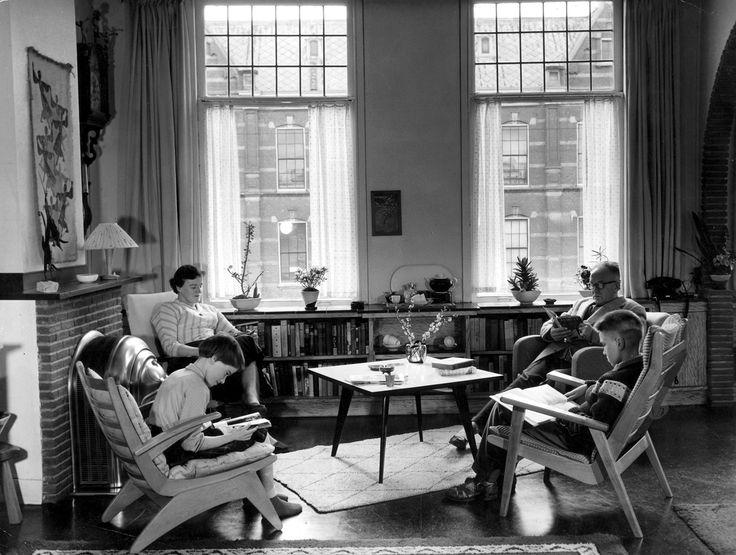 Huiselijk tafereel: lezend gezin in de woonkamer bij de haard 1957.