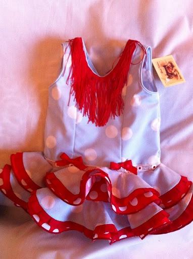 Vestido flamenca bebé , realizado en popelin celeste y combinado con volantes en rojo y blanco, pasacintas en el cuerpo y fleco en el escote.