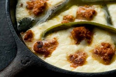 Queso flameado, which you might know as queso fundido, is a bubbling dish of melted white cheese, such as Monterey Jack or asadero, that's mixed with chiles and often chunks of chorizo or strips of fajita meat as well.