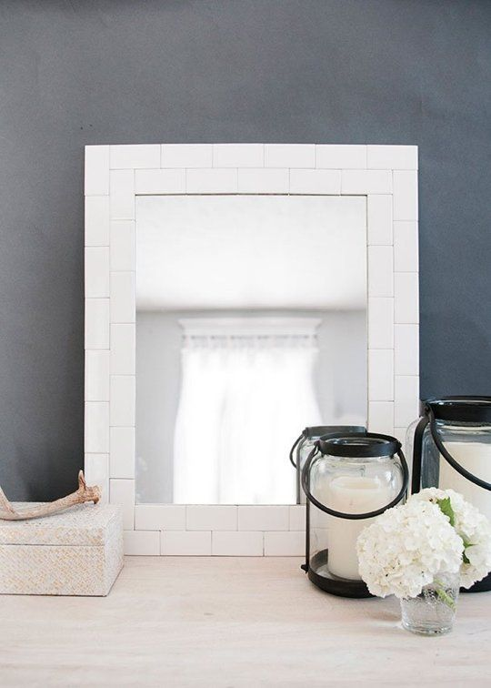 """8. Customize your bathroom mirror to make it more in keeping with the rest of the decor. Many vanity mirrors are plain, frameless affairs, but it doesn't take much to create something that looks like it was made for your space. Try """"framing"""" yours with molding, wrapping it in rope for a nautical effect, or adding subway tile like this one from House of Earnest."""