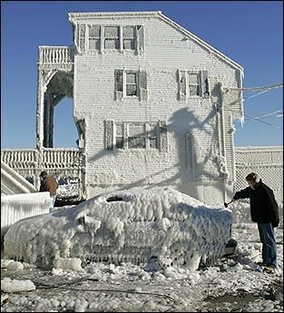 Hull, Massachusetts - John McDonald, of Quincy, uses a rubber hammer to clear ice from a friend's car.  Some residents spent Tuesday clearing ice from their homes following a blizzard that  dumped more than 3 feet of snow on some coastal towns in the state on Sunday. Jan. 2005