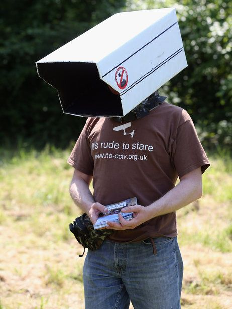 An anti-surveillance protester stands outside the Bilderberg conference last year in Watford, England.