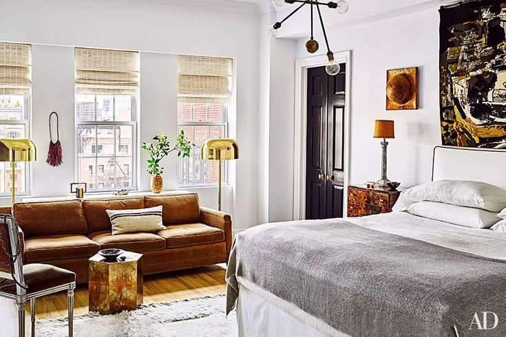 An Apparatus light fixture crowns the master bedroom, which is furnished with a 1950s Danish sofa, a circa-1970 brass table, and a vintage Italian brass floor lamp; the motorized window shades are by Bali.