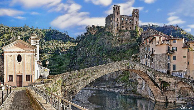 """L'emozionante visione del quartiere medievale della Terra e del Castello  dei Doria alto sulla Rocca, uniti all'opposta sponda del Nervia dal  magnifico ponte a schiena d'asino a un solo arco di 32 metri, definito da  Clude Monet nel 1884 """"un gioiello di leggerezza"""" -------------------------- The exciting vision of the medieval quarter of the Earth and the Castle Doria the top of the fortress, joined to the opposite side of the Nervia from magnificent humpback bridge with a span of only 32…"""