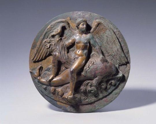 ~ Mirror cover with winged Eros.  Culture: Greek  Period: Early Hellenistic Period  Date: ca. 300 B.C.  Medium: Bronze