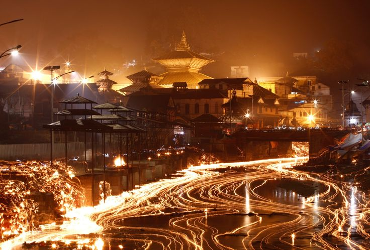 Масляные лампы освещают реку Багмати нафестивале Бала Чатурдаши, Катманду, Непал.