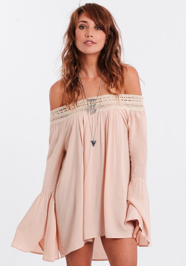 Sultry light pink dress featuring an off-the-shoulder silhouette with a crocheted elastic band in a beige hue. Finished with a subtle high-low hem and billowy bell sleeves.