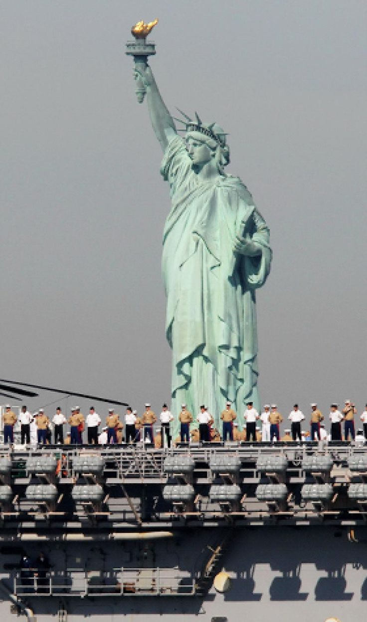 USS Iwo Jima, lined with Marines and sailors, passes the Statue of Liberty en route to Fleet Week.