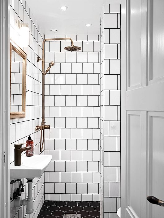 Hektagonkakel på golvet och vitt standardkakel med mörkfog på väggarna