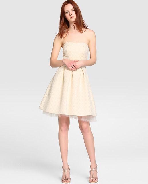 Vestido corto en color crudo con adorno de lurex. Tiene escote palabra de honor, pinzas en la falda y detalle de tul en el bajo.